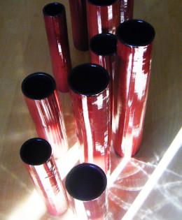 Riflessi su 'Giochi in Rosso', opera composta da più elementi di forma cilindrica